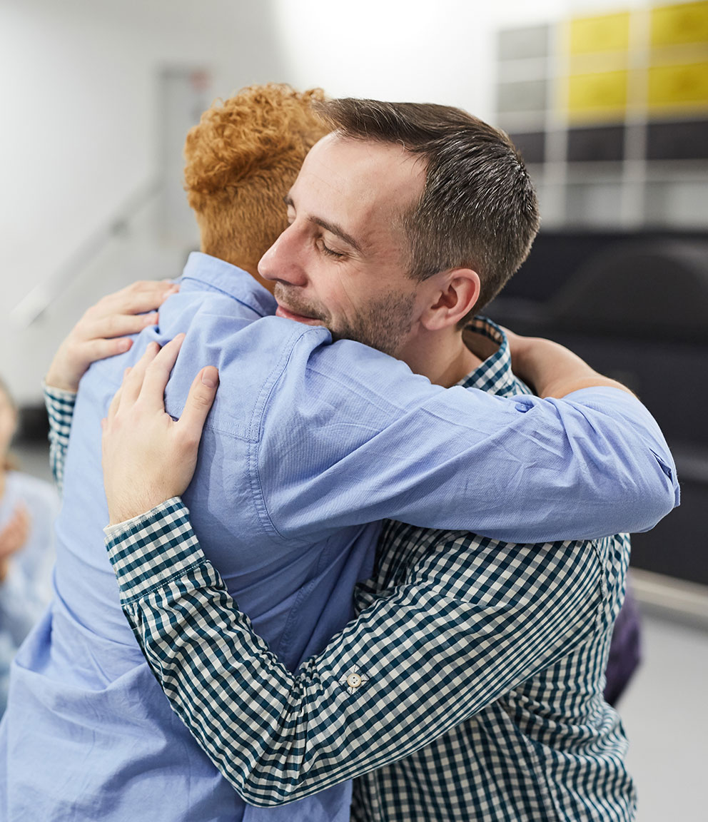 two men hugging and offering support