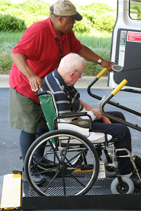 elderly man in wheelchair being helped into a van