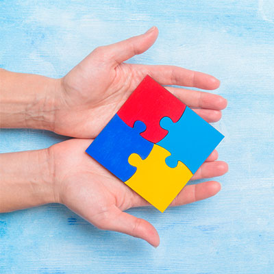 hand holding puzzle pieces together